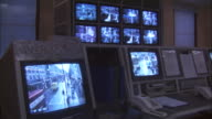 MS, Security surveillance monitors in control room at police station, London, England