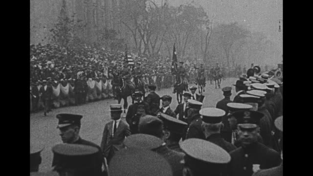 Seen from rear Gen John Pershing acknowledges crowd from open car as police motorcycles belch exhaust smoke with men waving straw boater hats from...
