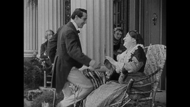 A dapper southern man greets his family on their porch