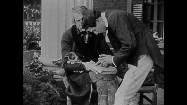 A southern father and son discuss a newspaper article while puppies crawl at their feet