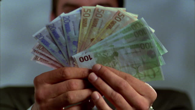 Selective focus close up tilt down man offering fanned stack of Euro notes