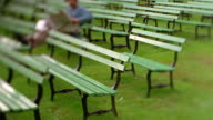 Selective focus pan man in turban reading paper on bench amongst large group of benches/ Nova Scotia