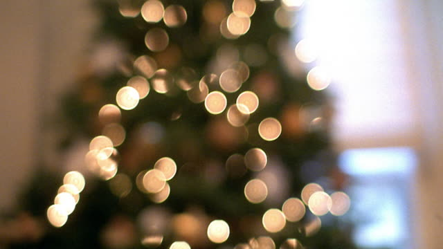 Selective focus tilt down from Christmas tree with lit ornaments to wrapped gifts