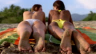 Selective focus two women lying on towel on beach / close up feet covered with sand