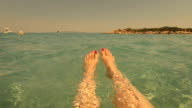 Selfie Beach Feet. Woman relaxing floating in the water.
