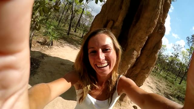 Selfie of caucasian female with enormous termite mound, Australia