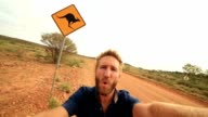 Selfie of young man in Australia standing near kangaroo crossing sign