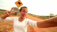 Selfie of young woman in Australia standing near kangaroo sign