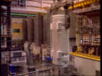 Sellafield row LIB Sellafield INT Container lifted by hoist from pool in plant Monitors in control room Container lifted across by hoist Drum...