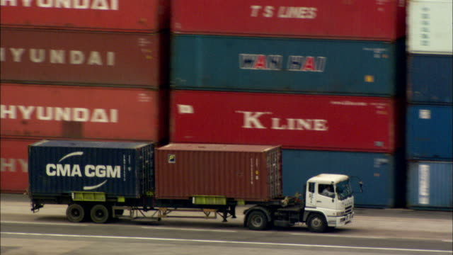 Semi trucks carry storage containers along a freight dock. Available in HD.