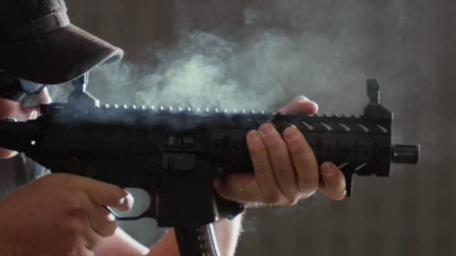 Semi-automatic machine gun is fired on a target range as spent cartridges and smoke flies in the air.