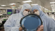 CU Semiconductor technicians inspecting wafer of integrated circuit boards / Bang Pa-In, Ayutthaya, Thailand