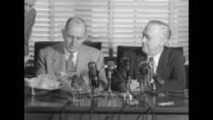 Senator Richard Russell Jr Chairman of the Senate Armed Service Committee sits down at table in front of microphones next to Senator Alexander Wiley...