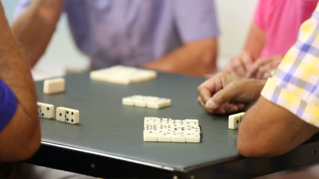 Senior adult couples playing dominoes together. Home or assisted living.