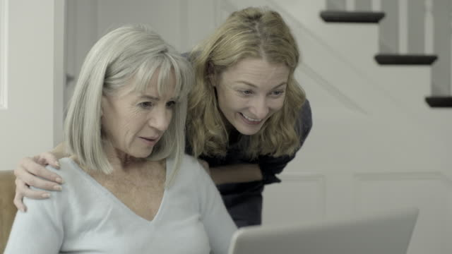 Senior Adult female looking at laptop with mature daughter