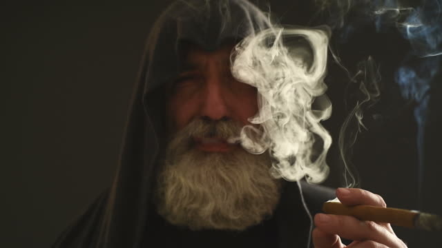 Senior Adult handsome man in a hood smoking a cigar on a gray background.