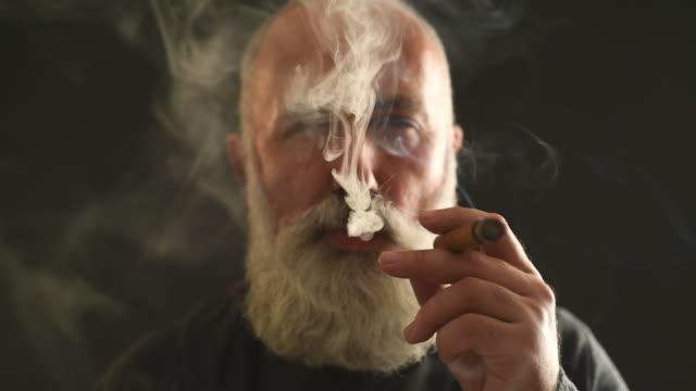 Aktiver Senior gut aussehender Mann Rauchen Sie eine Zigarre auf einem grauen Hintergrund.