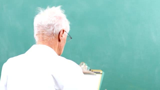 Senior adult man scientist, mathematician wearing lab coat with chalkboard.