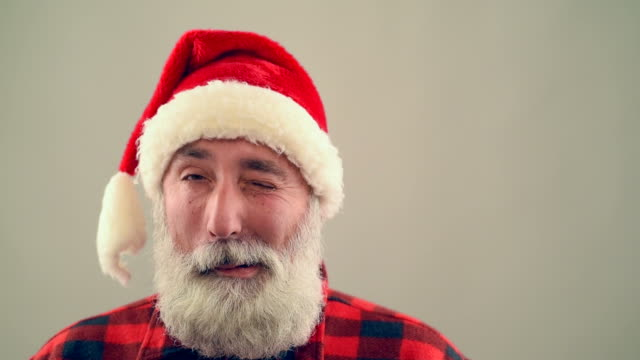 Senior adult man winking and smiling Santa Claus hat on a gray background.