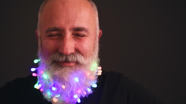 Senior adult man with a beard in black T-shirt elegant hat of Santa Claus looking at the camera shakes his head and fun