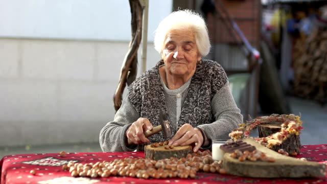 senior adult woman cracking hazelnut with hammer
