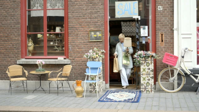 Senior adult woman leaving second-hand store with goods