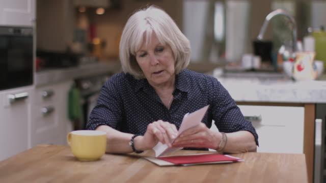 Senior adult woman opening bills at home