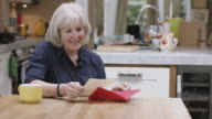 Senior Adult Woman opening Valentine's Day Card at kitchen table
