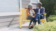 Senior African American couple chatting on bench