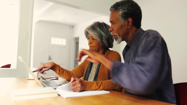 Senior Afrikaanse Amerikaanse echtpaar Financiën thuis bespreken