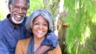Senior African American couple embracing, looking towards camera