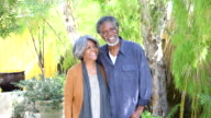 Senior African American couple in garden, smiling