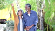 Senior African American couple in garden, woman smiling and reaching toward tree