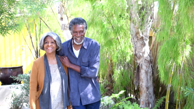 Senior African American couple in garden, woman touching tree