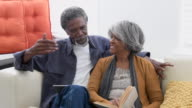 Senior African American couple on sofa talking affectionately