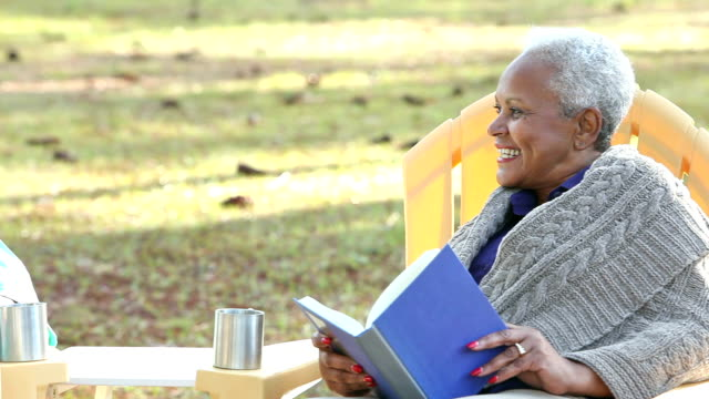 Senior African American couple outdoors reading, talking