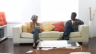 Senior African American couple sitting on sofa at home