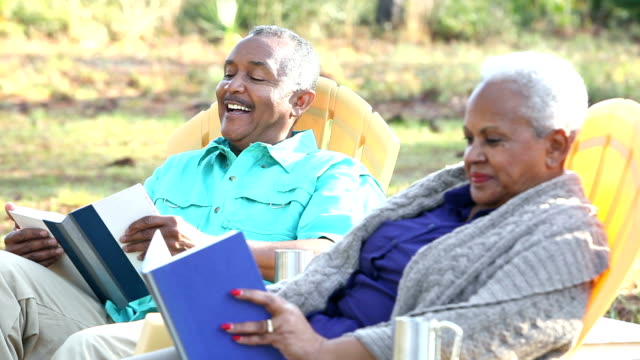 Senior African American couple sitting outdoors, reading