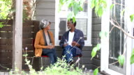 Senior African American couple sitting outside drinking water