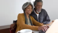 Senior African American couple using laptop at home