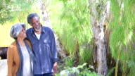 Senior African American couple walking in garden, smiling