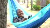 Senior African American man reading in hammock
