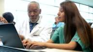 Senior African American professor tutoring nursing or medical student in class