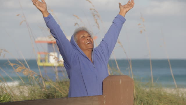 Senior African American woman at beach stretching