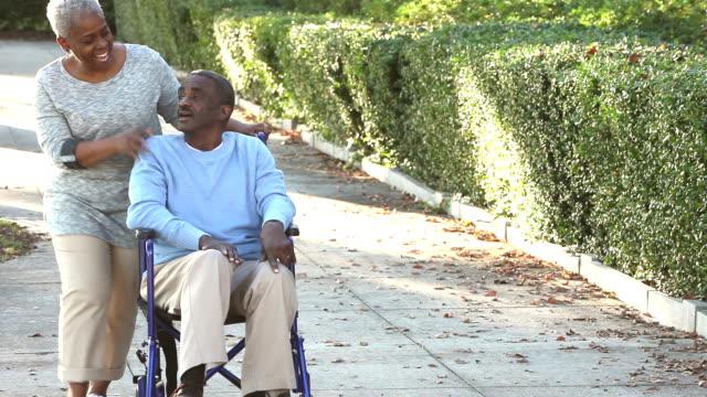 Senior-afroamerikanische Frau Mann im Rollstuhl schieben