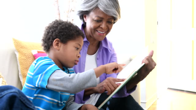 Senior African American woman showing book to grandson, smiling