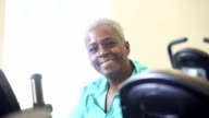 Senior African American woman working out in gym on exercise bike
