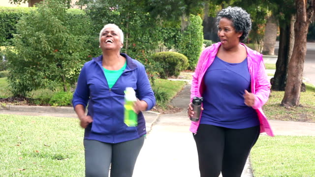 Senior African American women power walking, talking