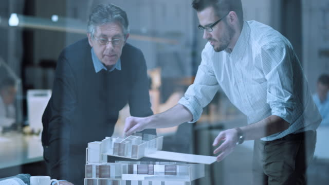 DS Senior and younger architect discussing architectural model details