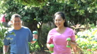 Senior Asian couple exercising, walking with handweights